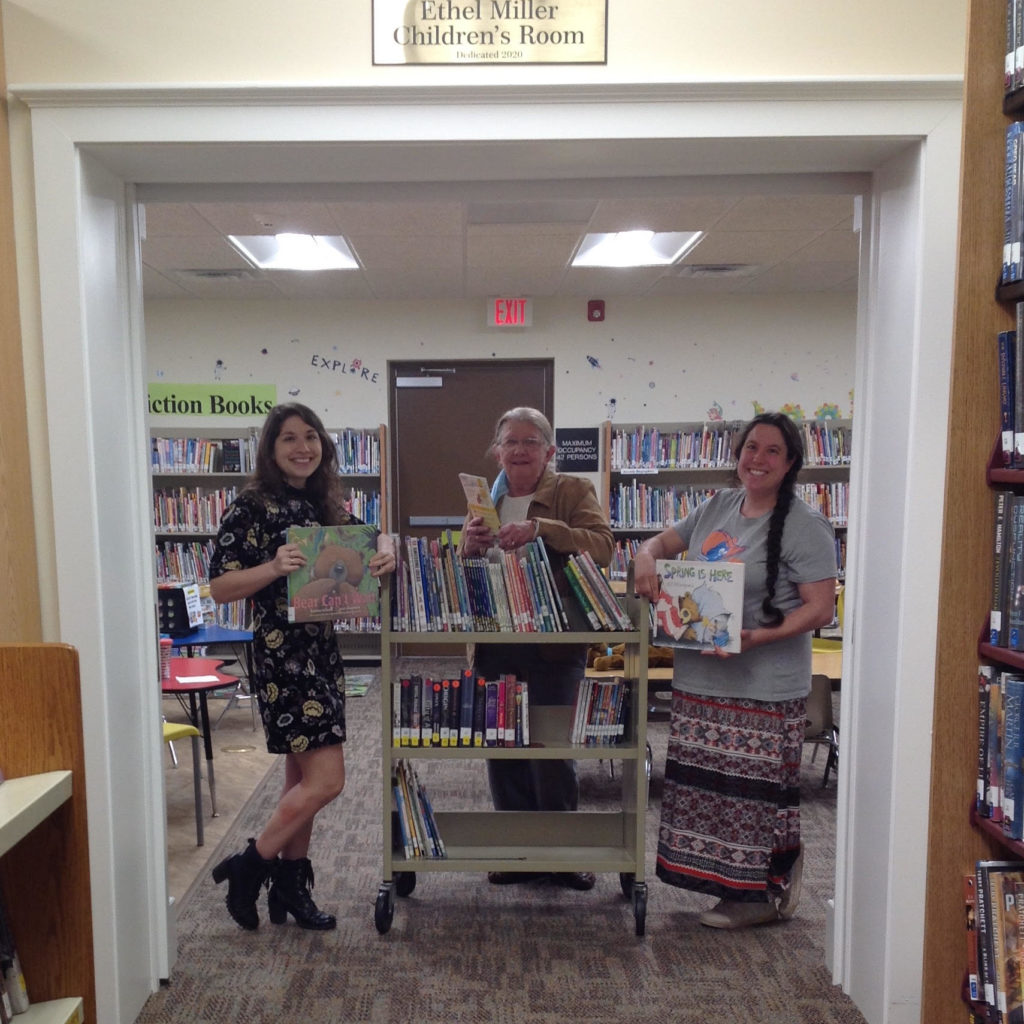 Three women smiling standing with Library cart in a library